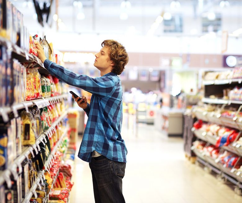 Man shopping in supermarket reading product